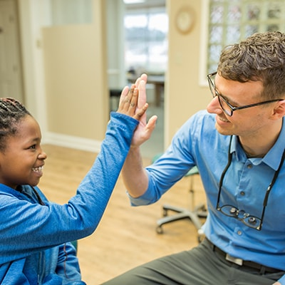 Dr. J high fiving a patient after the patient's services appointment